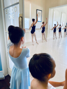 Two young students watch senior students at the barre in Studio One