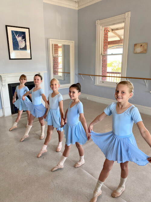 Ballet 1-4 students stand in a line showing their degage devant