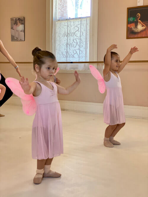 Two Dance & Performance students practicing their fairy wings